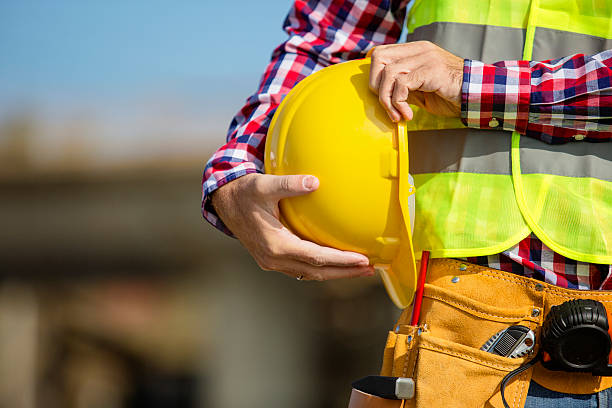Young construction worker holding a yellow helmet stock photo