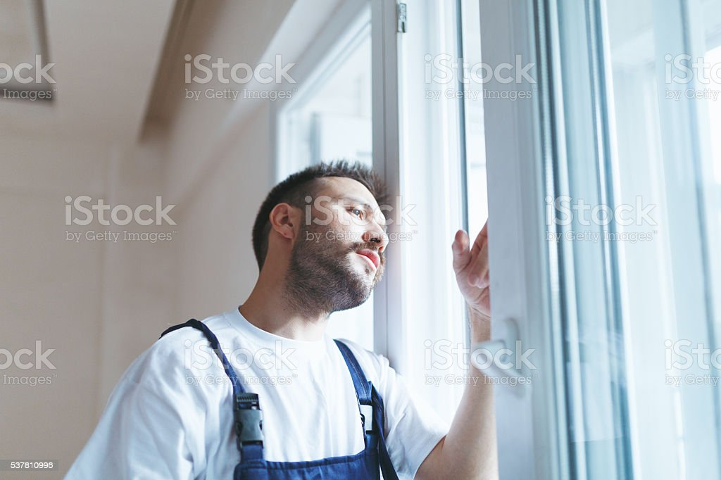 Young construction worker installing new windows stock photo