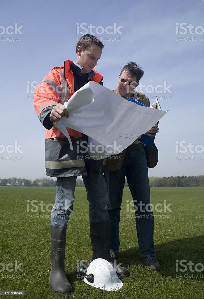Young construction worker on a building pit, and his manager royalty-free stock photo
