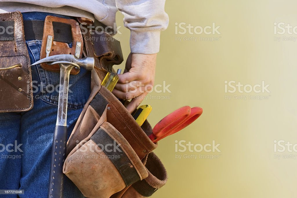 Young Construction Worker Reaches Into His Tool Belt Copy Space stock photo