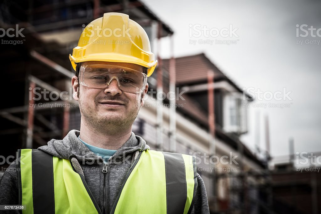 Young construction worker wearing hardhat on building site stock photo
