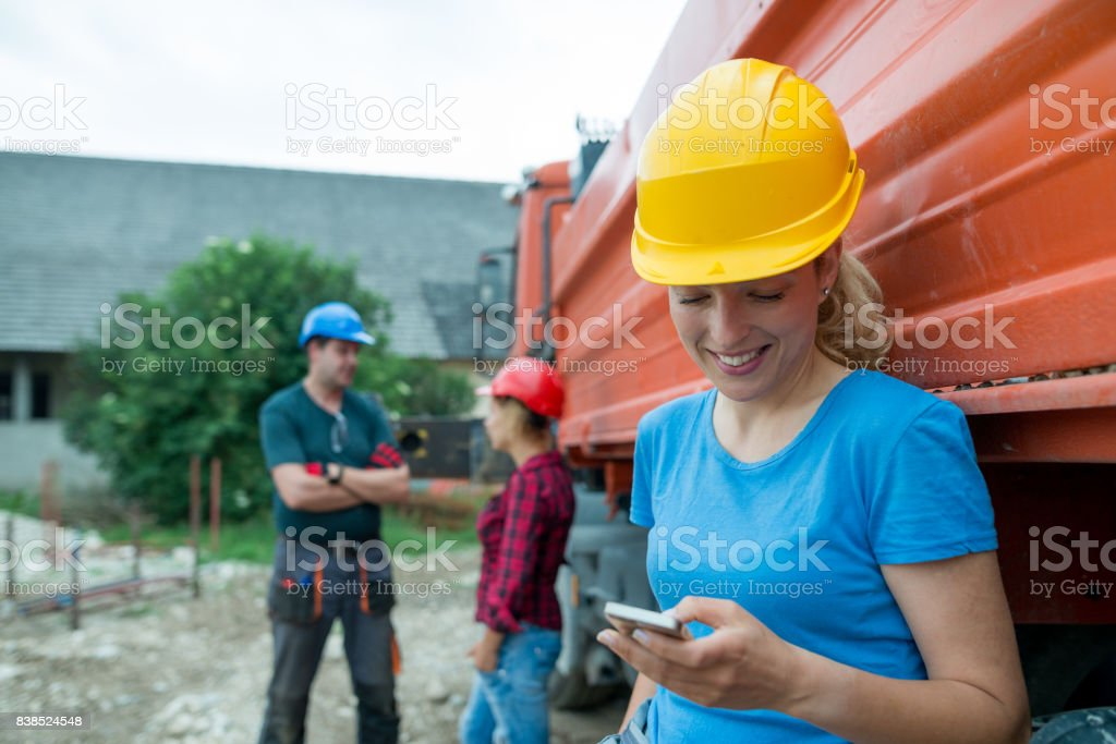 A young construction worker writes a text message during a break at a construction site stock photo