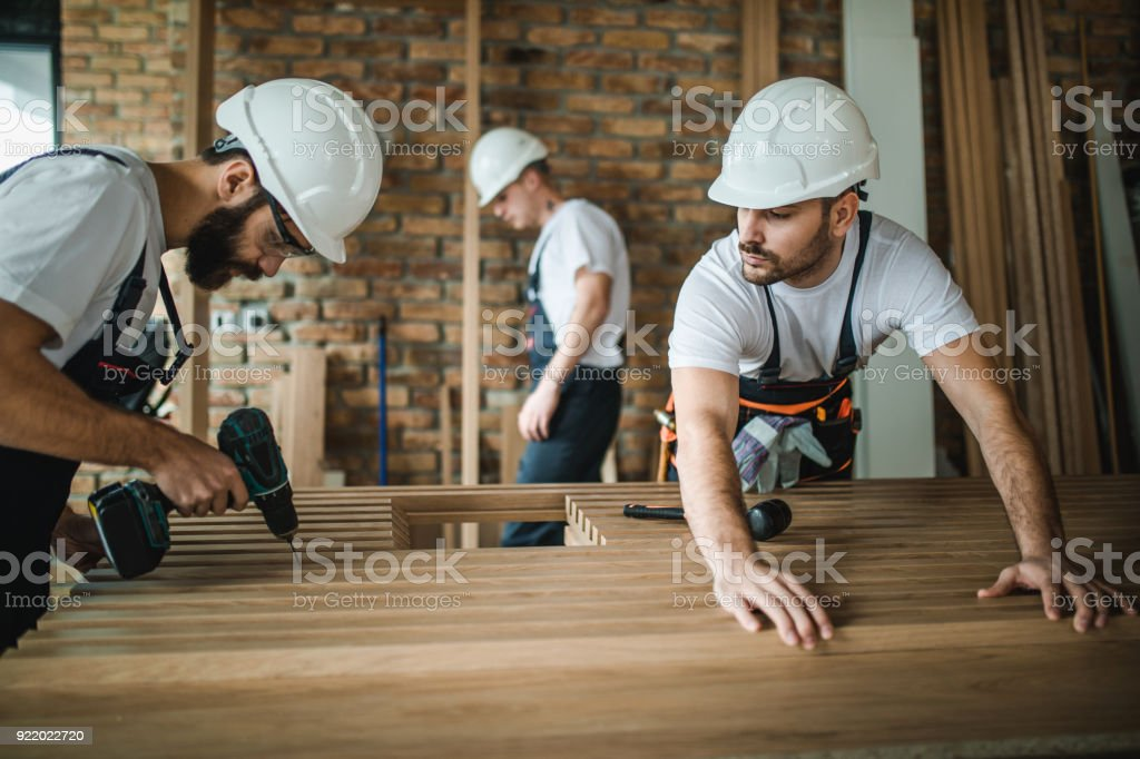 Young construction workers working on home renovation in the apartment. stock photo