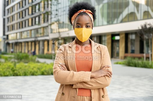 Young contemporary African businesswoman in elegant casualwear and protective mask crossing her arms on chest in urban environment