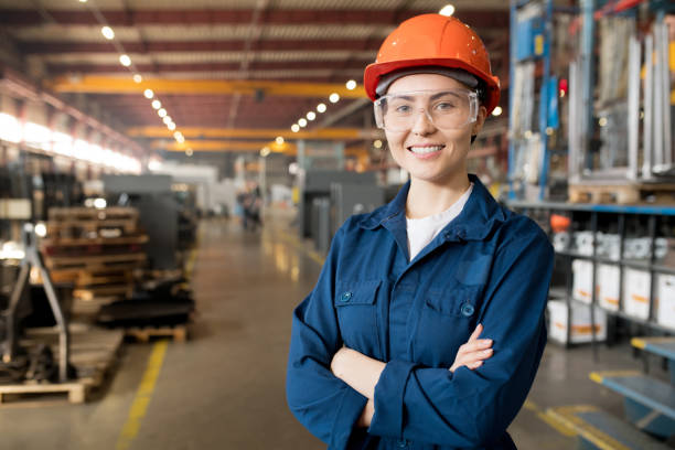 Young controler Young smiling female technician in blue uniform, protective eyeglasses and helmet working in modern factory engineer stock pictures, royalty-free photos & images