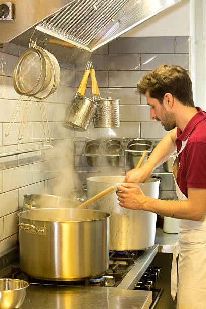 young cook stirring in big pot of boiling water - suppentopf stock-fotos und bilder