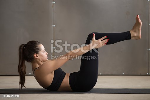 914755474 istock photo Young cool attractive woman in navasana pose, grey studio backgr 664635628