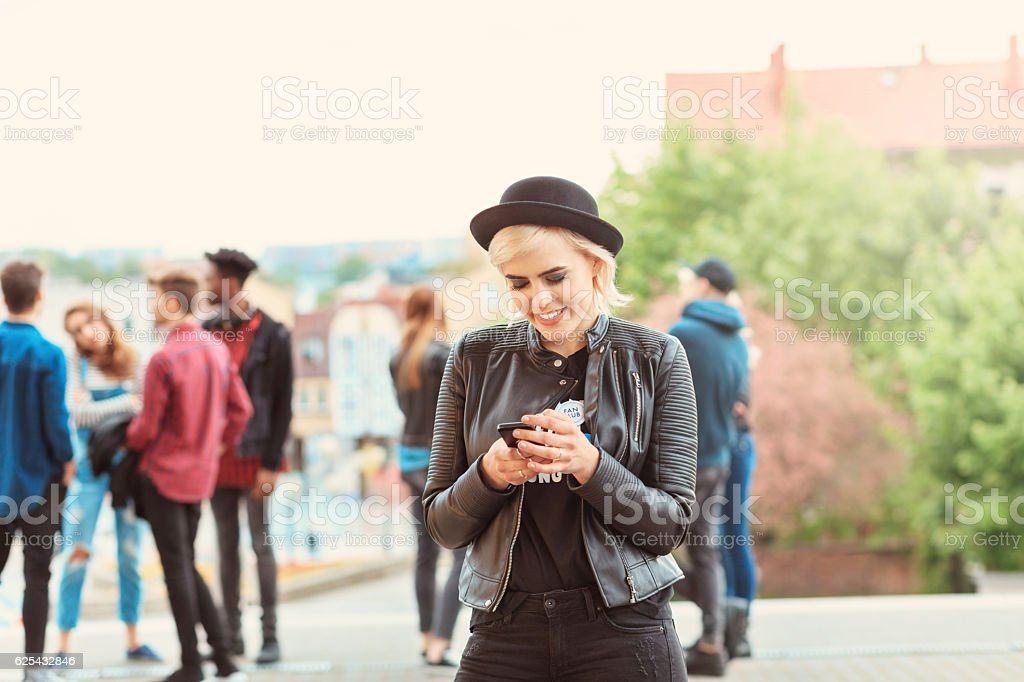 Young cool woman texting on mobile outdoor Funky young blonde woman wearing leather jacket and hat texting on smart phone outdoor. Multi ethnic group of people in the background. 20-29 Years Stock Photo