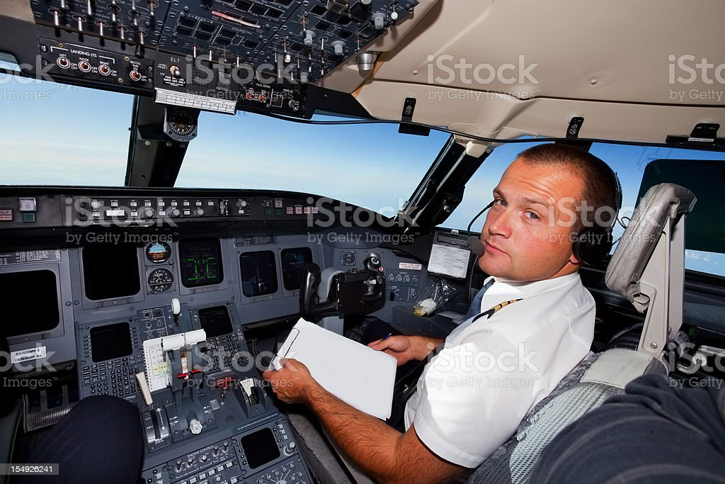 Young co-pilot at work in a cabin of commercial jet royalty-free stock photo