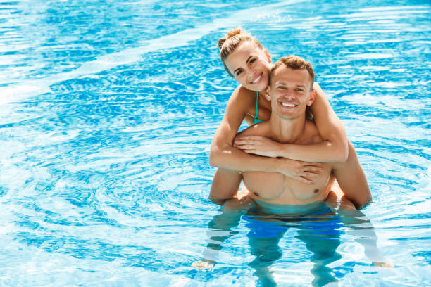 Young couple active leisure swimming pool concept stock photo