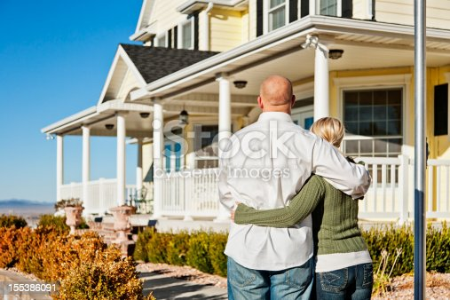 Photo of young couple standing in front of their new home, standing close together as they admire it.