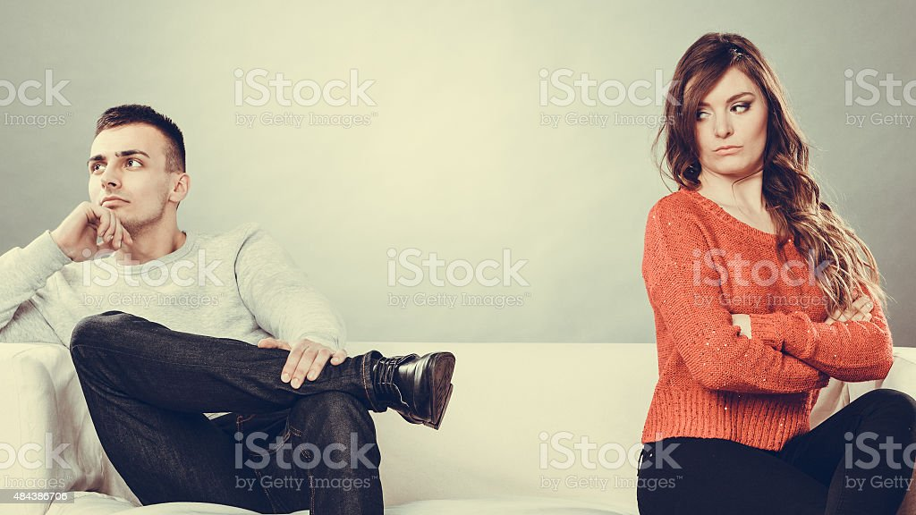 Young couple after quarrel sitting on sofa stock photo