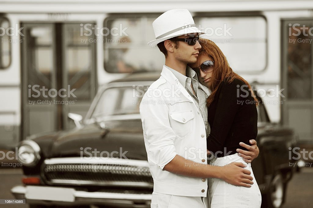 Young couple against a retro car royalty-free stock photo