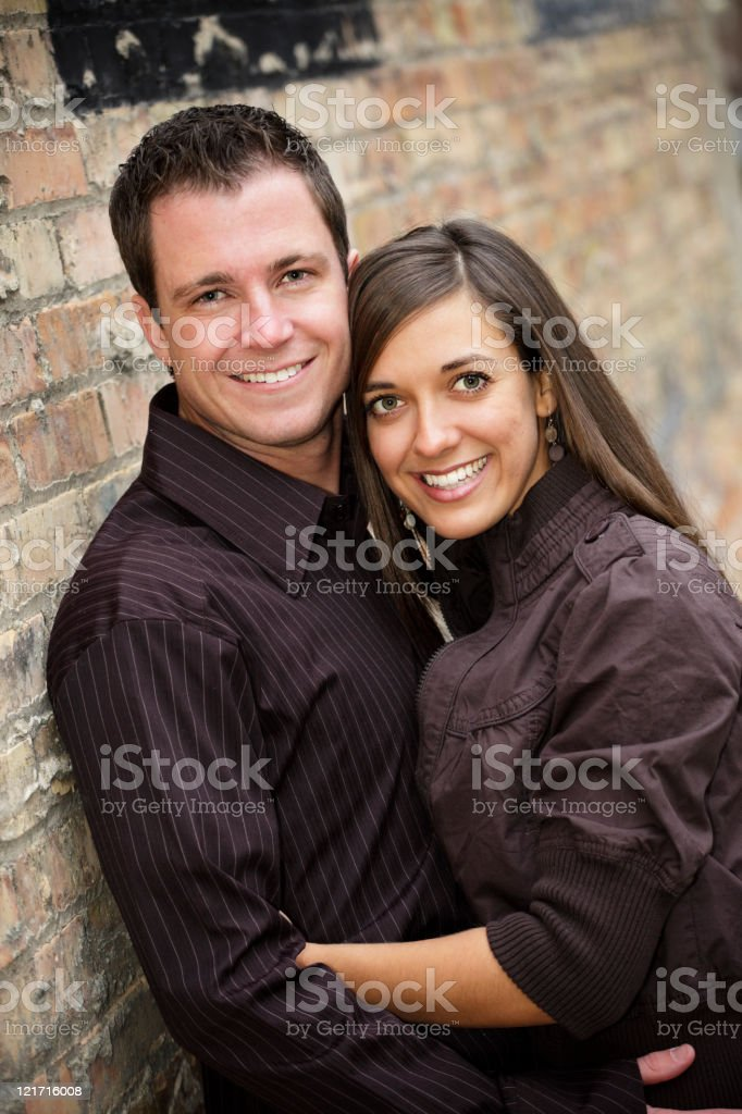 Young Couple Against Brick Wall royalty-free stock photo