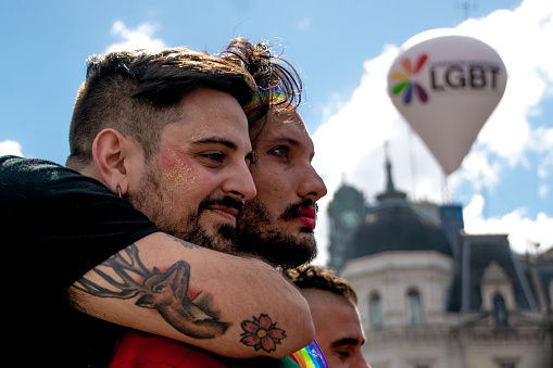 A young couple, an LGBT balloon, and Buenos Aires landmarks.