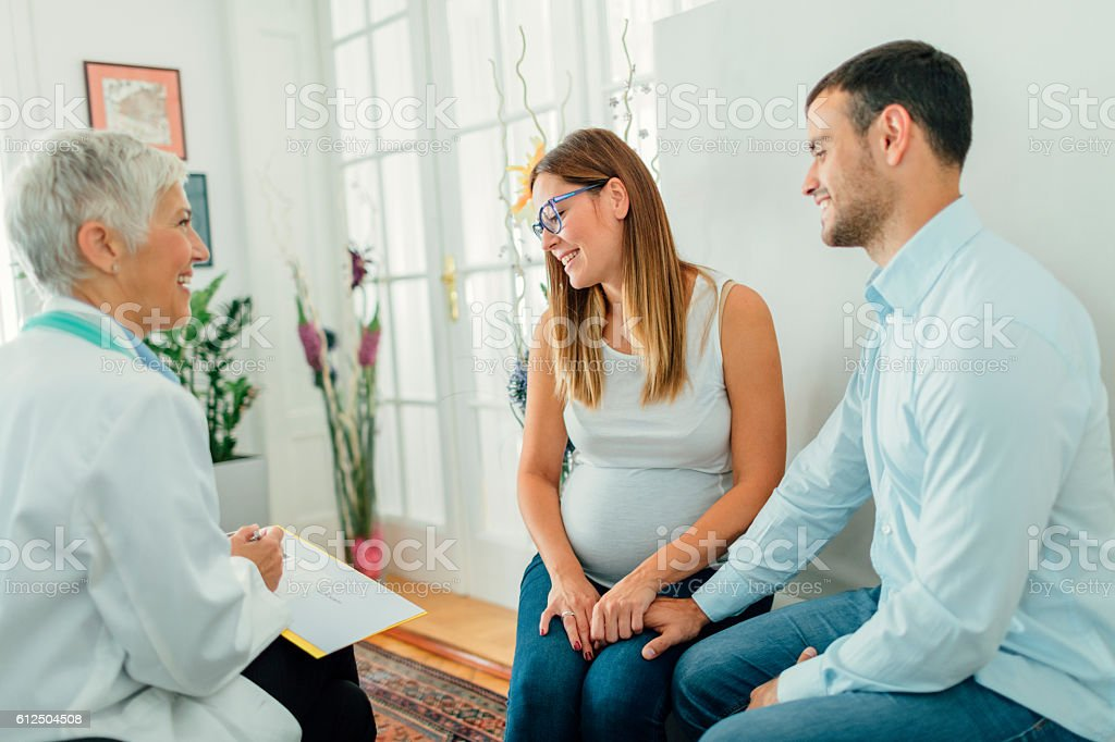 Young Couple And Female Doctor In A Consultation. stock photo