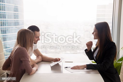 istock Young couple and female estate broker discussing property for sale 680437122