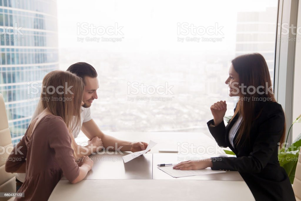 Young couple and female estate broker discussing property for sale stock photo