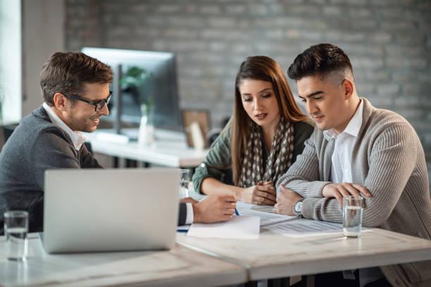 pareja joven y consultor financiero que va a través de planes de inversión durante una reunión. - planificación financiera fotografías e imágenes de stock