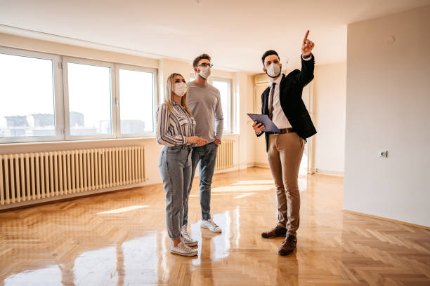 Young couple and male agent wearing face masks while looking a new real estate stock photo