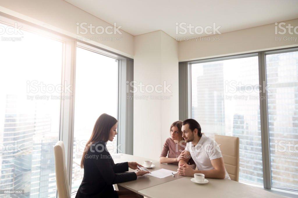 Jeune couple et agent immobilier gestionnaire de discuter le rapport contractuel - Photo