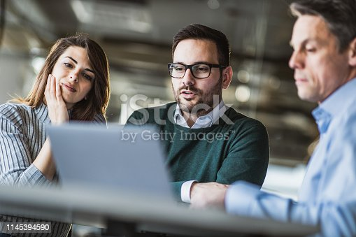 Young couple using computer with their insurance agent on a meeting in the office.
