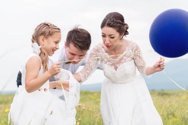 ein junges paar und ihre tochter in brautkleider sind fuß in der natur mit luftballons - hochzeitsspiele eltern stock-fotos und bilder