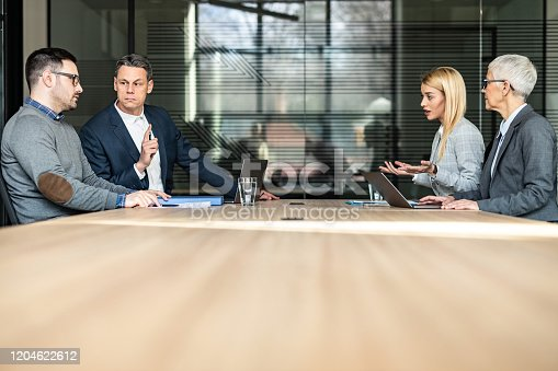 Young couple and their lawyers talking about the divorce during a meeting in the office. Copy space.