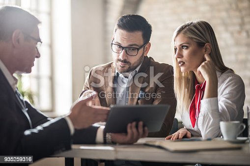 istock Young couple and their real estate agent looking at housing plan on touchpad in the office. 935259316