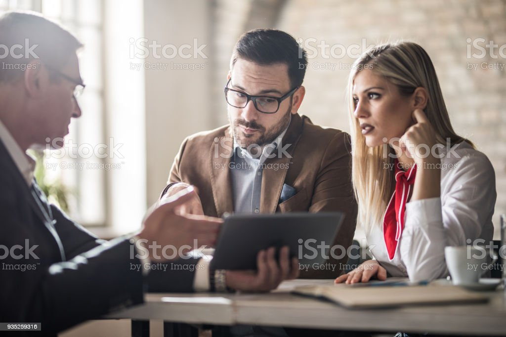 Young couple and their real estate agent looking at housing plan on touchpad in the office. stock photo