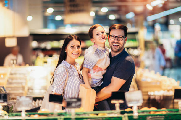 Young couple and their son buying products in supermarket stock photo