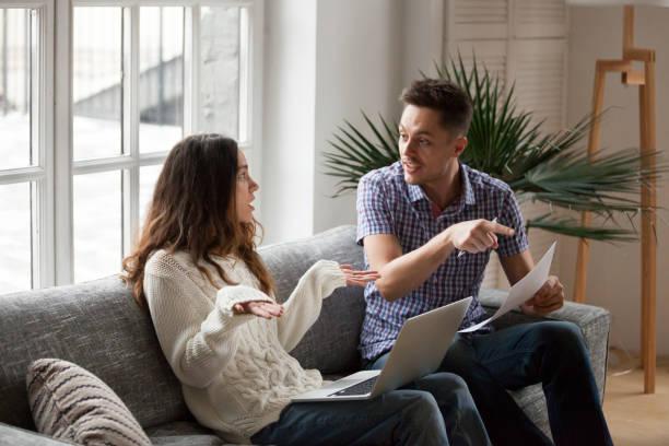jong koppel ruzie over hoge rekeningen met laptop en documenten - couple fighting home stockfoto's en -beelden