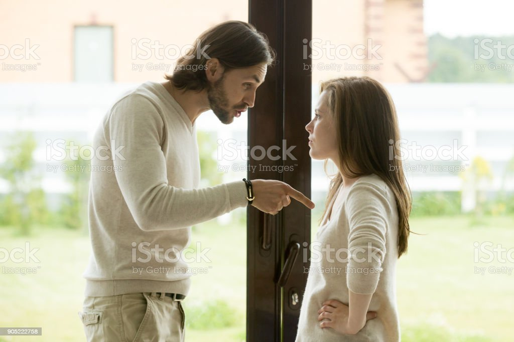 Young couple arguing at home, man pointing finger blaming woman stock photo