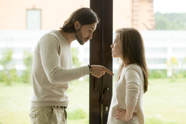 young couple arguing at home, man pointing finger blaming woman - husband stock pictures, royalty-free photos & images