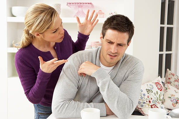young couple arguing in their home - echtgenote stockfoto's en -beelden