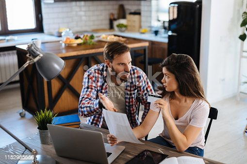 istock Young couple arguing while having problems with paying their bills over Internet 1152985556