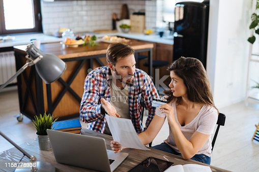 istock Young couple arguing while having problems with paying their bills over Internet 1158778936