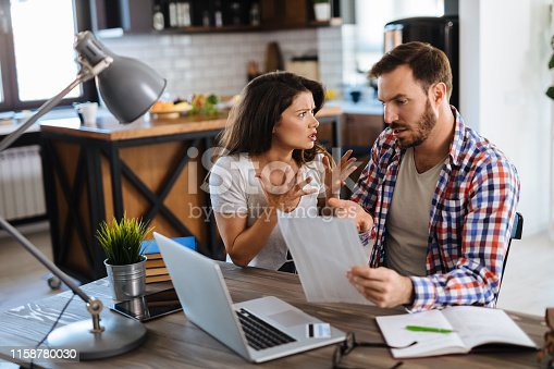 istock Young couple arguing while having problems with paying their bills over Internet 1158780030
