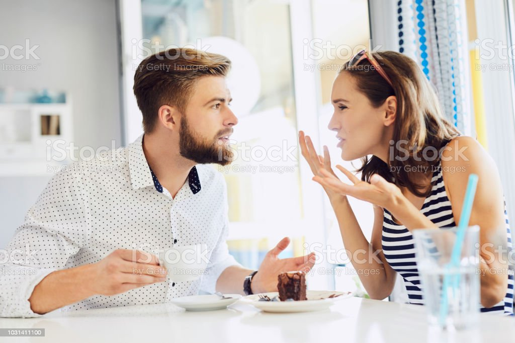 young couple arguing while sitting and drinking coffee in restaurant stock photo