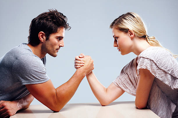 young couple arm wrestling against grey background - man dominating woman stock photos and pictures