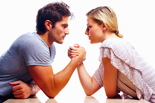 young couple arm wrestling against white background - man dominating woman stock photos and pictures