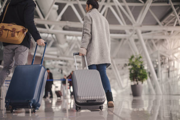 young couple arriving at the airport - luggage stock photos and pictures