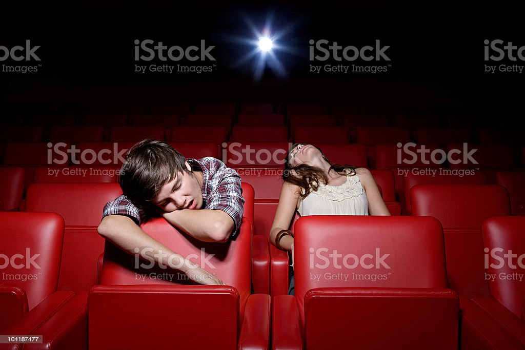 Young couple asleep in the movie theater stock photo