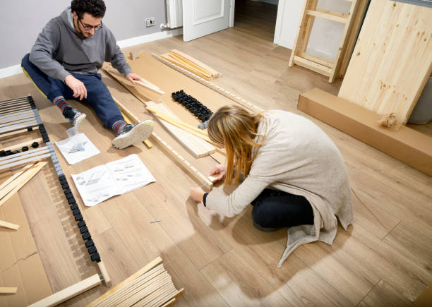 Young couple assembling bed in new house stock photo