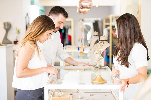 young couple at a jewelry store - diamanten kaufen stock-fotos und bilder