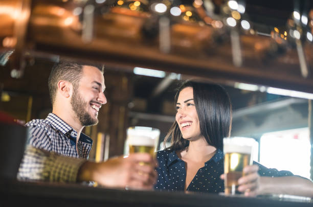 Young couple at beginnings of love story - Pretty woman drinking beer with handsome man at pub - Relationship lovers concept with drunk boyfriend and girlfriend together at brewery - Warm retro filter stock photo