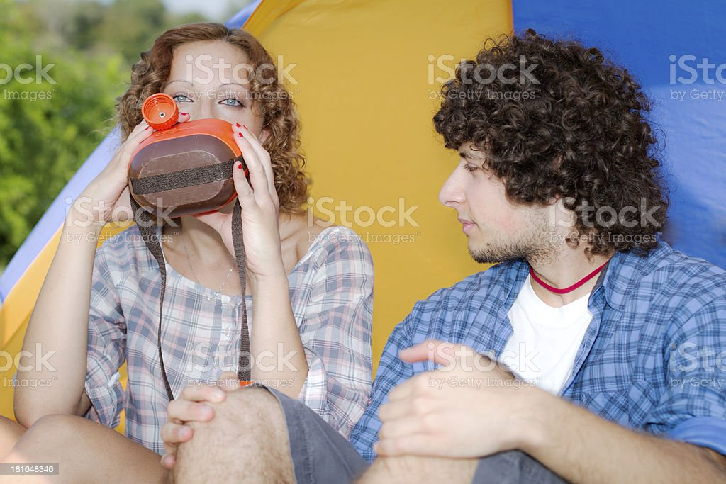 Young couple at camping drinking from water canteen royalty-free stock photo