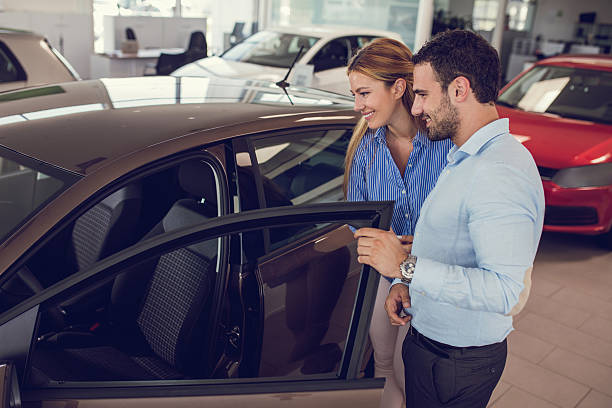 Young couple at car dealership looking at new car together. - foto de stock