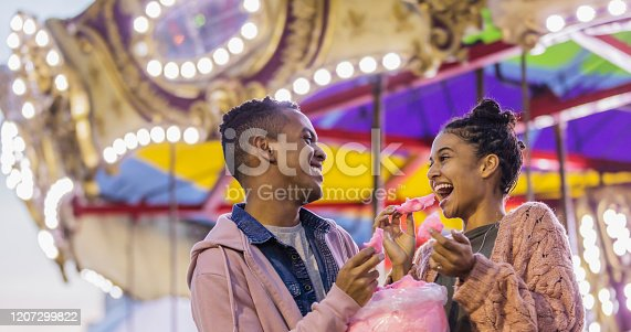 A young couple in their 20s having fun together at a traveling carnival. An amusement park ride is out of focus in the background. They are eating cotton candy. He is African-American and his girlfriend is mixed race African-American and Caucasian.