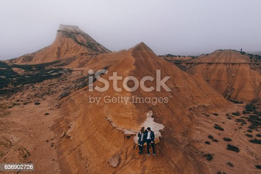 A young couple sitting together on a desert road